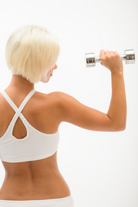 Back view portrait muscular blond woman holding dumbbell on white