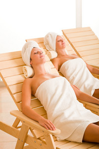 Spa luxury relax room two beautiful women lying on sun-beds
