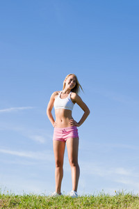 Sportive stretching young happy woman meadows blue summer sky