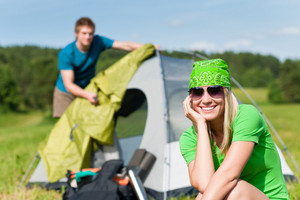 Young camping couple build-up tent in summer meadows countryside