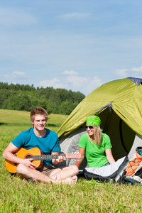 Happy camping couple sitting by tent play guitar sunny countryside