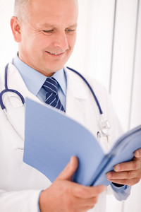 Professional senior doctor male with stethoscope look down document folders