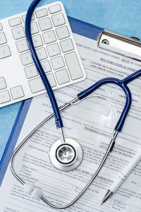 Stethoscope laying over doctors emergency report medical documentation