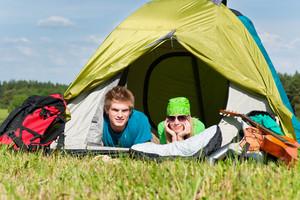 Happy camping couple lying inside tent backpack in sunny countryside