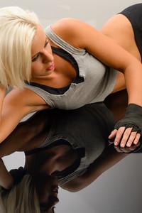 Female kick-boxer laying down on black plexiglass fitness studio