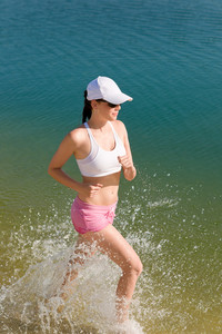 Summer active woman jogging on beach seashore in fitness outfit