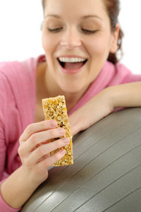 Fitness happy woman eat granola bar sportive outfit in gym