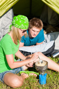 Young camping couple cooking meal outside tent in sunny countryside