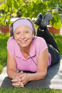 Senior sportive woman on mat listen music outside sunny day