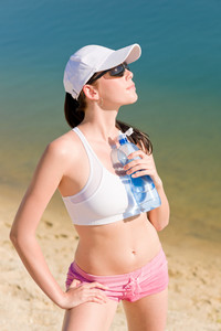 Summer beach active woman enjoy sunset sitting in fitness outfit