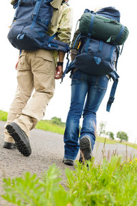 Close-up of hiking couple legs backpack on asphalt road