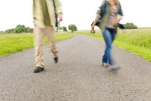 Close-up blurred portrait hiking couple legs backpack on asphalt road