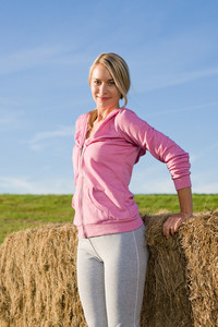 Portrait of sportive young woman relax lean against hay bales