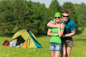 Young camping couple hugging in summer countryside tent in background