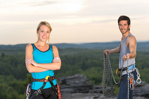 Active young couple rock climbing reach top at sunset