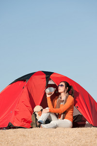 Camping happy woman front of tent on beach blue sky