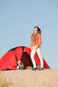 Camping happy woman in tent on beach blue sky