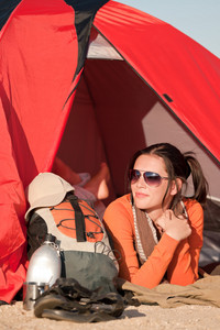 Camping happy woman in tent on beach during sunny day