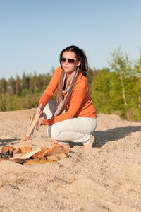 Camping happy woman make campfire on beach blue sky