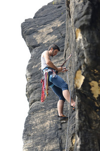 Rock climbing fit man on rope  sunny day