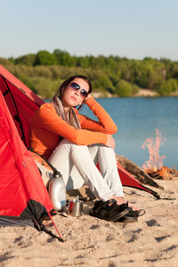 Camping happy woman sitting by campfire relaxing in tent