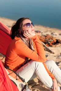 Camping happy woman sitting by campfire relaxing on beach