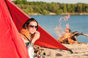 Camping happy woman relax lying in tent by  campfire