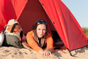 Beautiful happy woman camping lying and relaxing in tent