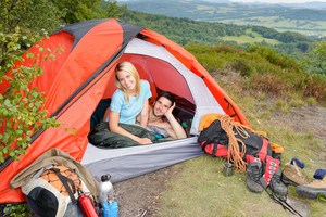 Camping young couple backpackers in tent with climbing gear sunset