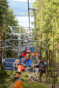 Chairlift going through forest with young people