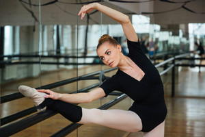 Charming ballerina doing stretching exercisesin ballet class