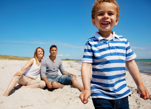 Charming kid together with his mom and dad on a summer vacation