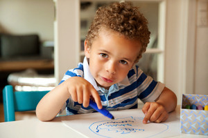 Charming toddler busy doing his art activity at his desk
