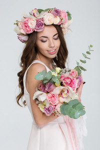Charming young bride with long curly hair in wreath of roses looking at flower bouquet over white background