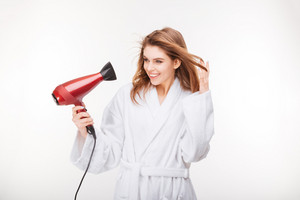 Cheeful lovely young woman in bathrobe standing and drying her hair with dryer over white background