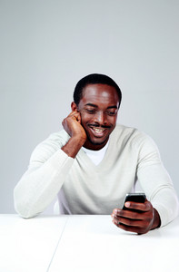 Cheerful african man sitting at the table and using smartphone