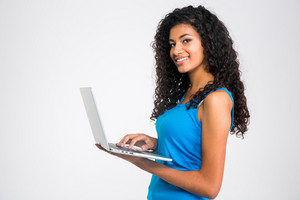 Cheerful afro american woman using laptop