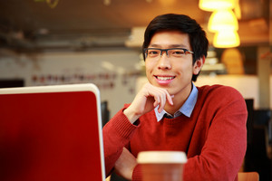 Cheerful asian man sitting at the table with laptop and looking at camera