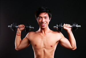 Cheerful asian man working out with dumbbells on black backgroung