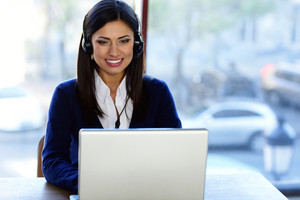 Cheerful beautiful call-center assistant at the desk