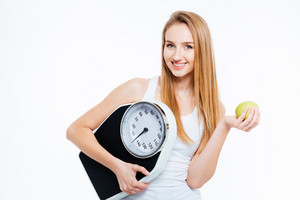 Cheerful beautiful young woman holding scales and green apple over white background