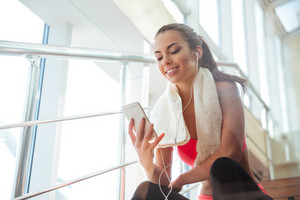 Cheerful beautiful young woman sitting on stairs in gym and listening to music