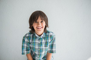 Cheerful boy in checkered shirt in front of a white wall