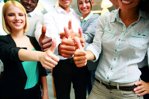 Cheerful business group giving thumbs up