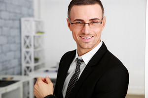 Cheerful businessman in glasses standing at office