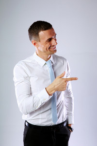 Cheerful businessman pointing at something on gray background