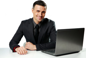Cheerful businessman sitting at the table with laptop isolated on a white background
