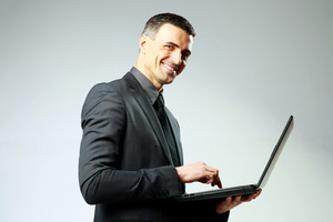Cheerful businessman using laptop on gray background