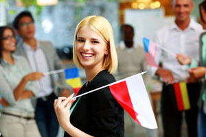 Cheerful businesswoman holding flag of Poland in front of colleagues