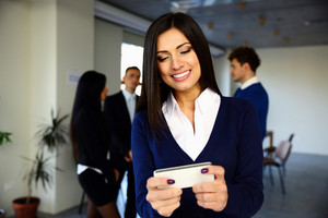 Cheerful businesswoman using smartphone in front of colleagues